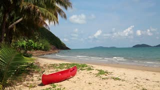 Red canoe on the beautiful tropical beach with palm trees