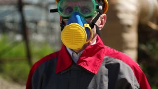 Repairman in hard hat, goggles and respirator at industrial area. Worker in yellow hard hat, goggles and respirator at heat electric power station. Chemical protection
