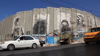 Security wall in Bethlehem, Israel. Gray walls painted with bright colorful graffiti
