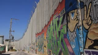 Security wall in Bethlehem, Israel (Palestinian National Authority). Gray walls painted with bright colorful graffiti
