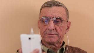 Senior man communicates via smartphone. Man on a sofa with a white smartphone. Man using webcam on smartphone