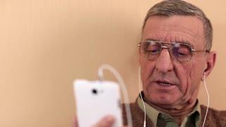 Senior man communicates via smartphone. Man on a sofa with a white smartphone. Man with smartphone communicates through skype. Man using webcam on smartphone