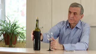 Senior man in blue shirt sits at the table and pours wine in glass. Grey-haired senior man drinks wine. Man with smartphone drinking wine. Man with white mobile phone and bottle of wine