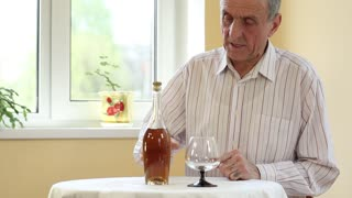 Senior man in white shirt sits at the table and pours brandy in glass