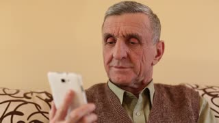 Senior man looking and flipping through the photos in her smartphone. Senior man using white cell phone