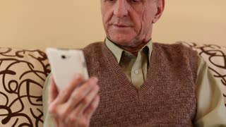 Senior man looking and flipping through the photos in her smartphone. Senior man using white smartphone