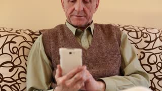 Senior man looks and flips through the photos in her smartphone. Senior man uses white cell phone