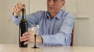 Senior man sits at a table and drinks wine. Man in blue shirt with bottle of wine