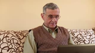 Senior man types text using laptop. Man on a divan with notebook