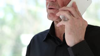 Senior man with white smartphone. Man talking on a cell phone with a serious look of face