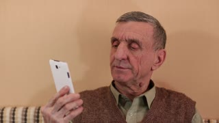 Senior man with white smartphone speaks smiling and gesticulating