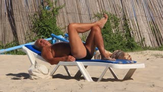 Senior sunbathes on a beach. Get a tan