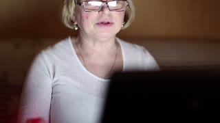 Senior woman communicates using laptop. Woman with notebook