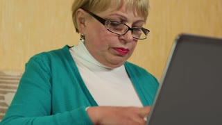 Senior woman in glasses types text using laptop and smoking a cigarette. Woman with laptop and a cigarette