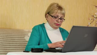 Senior woman in glasses types text using laptop and smoking a cigarette. Woman with laptop and cigarette