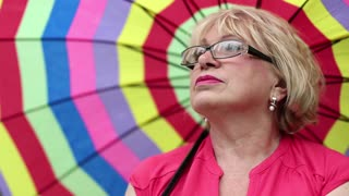 Senior woman in glasses with colorful umbrella looking into the distance