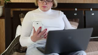 Senior woman in glasses with laptop and cell phone. Businesswoman with mobile phone and notebook. Female with smartphone and laptop sits on a sofa
