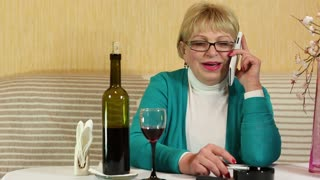 Senior woman in glasses with white cell phone speaks, drinks and smokes