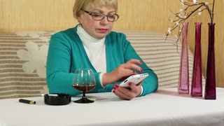 Senior woman in glasses with white smartphone speaks and drinks brandy