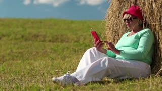 Senior woman in red cap sits on a green grass near haystack and uses red smartphone. Woman with red mobile phone