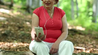 Senior woman in red hat sits on a fallen tree in forest and communicates via smartphone