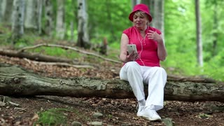 Senior woman in red hat sits on a fallen tree in the forest and communicates via smartphone