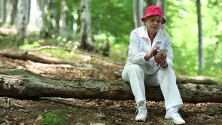 Senior woman in red hat sits on a fallen tree in the forest and uses smartphone
