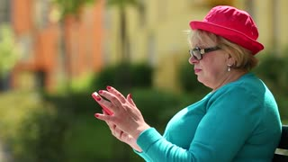 Senior woman in red hat sits on the bench and uses red smartphone. Woman looking and flipping through the photos in her cell phone