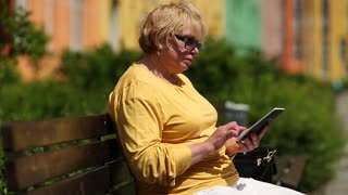 Senior woman in yellow jacket sits on the bench in courtyard and uses e-book. Woman holds electronic book