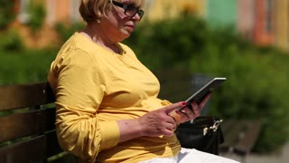 Senior woman in yellow jacket sits on the bench using e-book. Woman holding electronic book