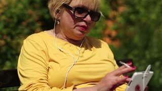 Senior woman in yellow shirt with cigarette sits on the bench and uses white smartphone