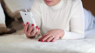 Senior woman lies on the bed and communicates via smartphone. Blonde woman talks on smartphone with webcam. Woman with phone communicates through skype. Businesswoman with mobile phone