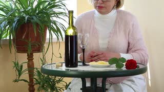 Senior woman sits at a table drinking red wine and eating cheese