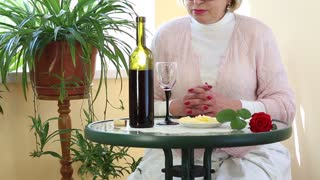 Senior woman sits at a table drinking wine and eating cheese