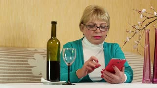 Senior woman sits at the table, drinks red wine and speaks on smartphone
