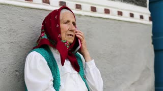 Senior woman sits near grey wall of his house and talks on mobile phone. Old woman sits on bench near his house and speaks on cell phone. Ukrainian old woman with smartphone. Female with smartphone