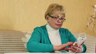 Senior woman sits on a divan and uses white mobile phone. Senior woman looks and flips through the photos in her smartphone. Female with smartphone