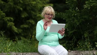 Senior woman sits on a fallen tree and communicates via tablet computer. Woman with tablet PC
