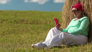 Senior woman sits on a green grass near haystack and communicates via cell phone. Woman with red smartphone communicates via internet