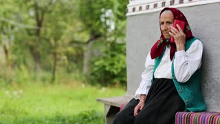 Senior woman sits on bench and talks on mobile phone. Old woman sits on bench near his house and speaks on cell phone. Ukrainian old woman with red smartphone. Female with smartphone. Roar of laughter