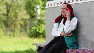 Senior woman sits on bench and talks on mobile phone. Old woman sits on bench near his house and speaks on cell phone. Ukrainian old woman with red smartphone. Female with smartphone
