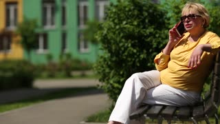 Senior woman sits on the bench and communicates via cell phone