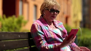 Senior woman sits on the bench and communicates via smartphone