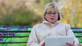 Senior woman sits on the bench and communicates via tablet computer. Woman with tablet PC, and she is in a merry mood