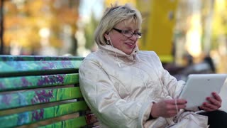Senior woman sits on the bench and communicates via tablet computer. Woman with tablet PC. She is in a merry mood