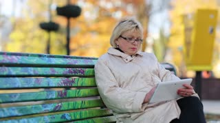 Senior woman sits on the bench and uses tablet computer. Woman with Tablet PC