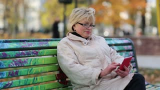 Senior woman sits on the bench in autumnal city park and uses smartphone. Woman with red smartphone. Female with cell phone. Businesswoman with mobile phone