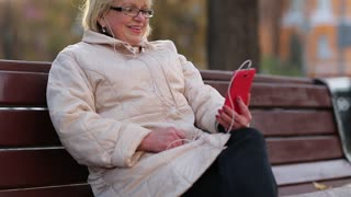 Senior woman sits on the bench near the road and communicates via smartphone