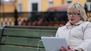 Senior woman sits on the bench near the road and communicates via tablet computer. She is in a merry mood. Woman with Tablet PC sits on the bench and talks on Skype. Pleasant conversation on Skype