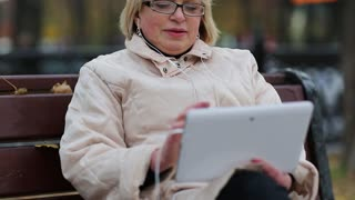 Senior woman sits on the bench near the road and communicates via tablet computer. She is in a merry mood. Woman with tablet PC